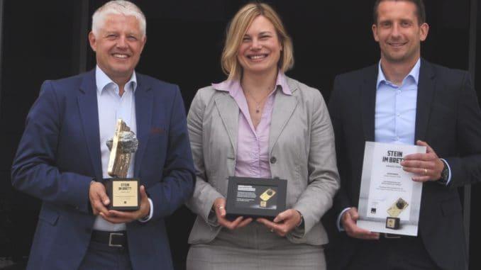 """Über den """"ibau Stein im Brett Award 2018"""" in der Kategorie Bodenbeläge Holz und Laminate freuen sich Bernd Reuß (l.), Presseverantwortlicher bei der Hamberger Flooring GmbH & Co. KG, zusammen mit den Vertretern der ibau GmbH Anja Rößler und Rüdiger Koch."""